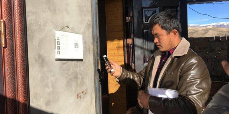 A government official scanning a QR code on the wall of a house in Xinjiang that gives him access to the residents' personal information.