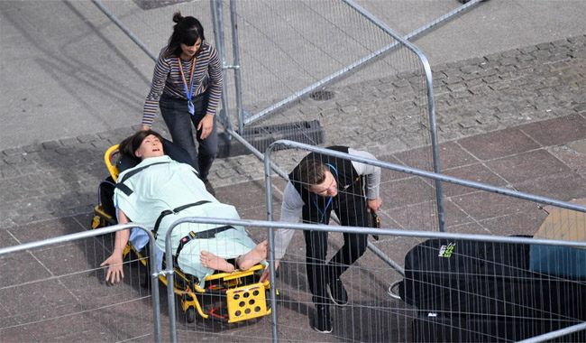 A dummy to help medics tackle the virus is wheeled into the new hospital  Credit: EPA