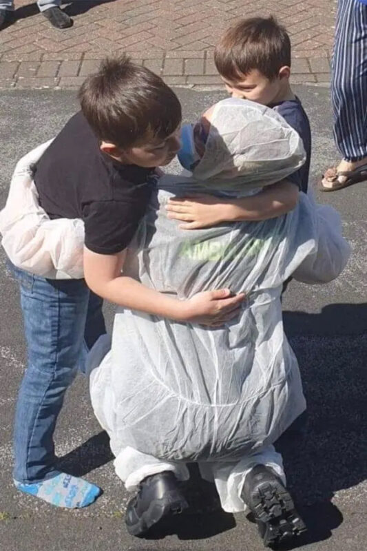 One heartbreaking image shows Joanne dressed in scrubs, PPE, and a mask, hugging and kissing the two boys.